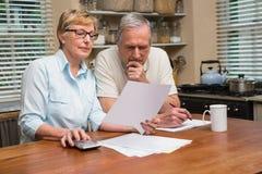 制定出他们的票据的资深夫妇 免版税库存图片
