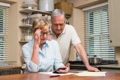 制定出他们的票据的资深夫妇 免版税库存照片