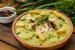 制成菜泥汤用豌豆、熔化乳酪、烤肉、油煎方型小面包片和草本 木背景 顶视图 特写镜头 库存照片