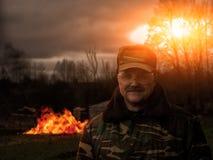 制服的一个人用火武装 爱开玩笑的人的微笑 在背景中,大厦烧伤 免版税库存照片