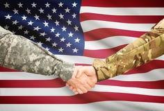 制服的人与在背景-美国的旗子握手 图库摄影