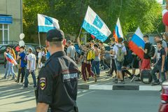 制服的俄国警察有在街道上的一枚徽章的在抗议,从后面的看法集会  图库摄影