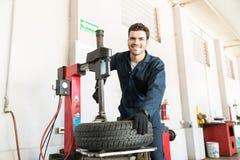 制服的军人使用在车库的轮胎更换者 图库摄影