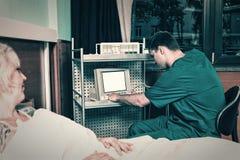 制服的医生看医疗设备显示器,当时 免版税库存图片