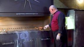 制服的厨师在格栅上把串放用生肉在餐馆厨房 股票视频