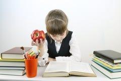 制服的女小学生读书并且吃红色苹果 免版税库存照片