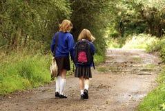 制服的女小学生走到学校的 免版税图库摄影