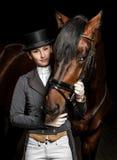 制服的女骑士有一匹棕色马的在槽枥 免版税库存图片