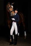 制服的女骑士有一匹棕色马的在槽枥 库存图片