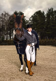 制服的女骑士有室外一匹棕色的马的 库存图片