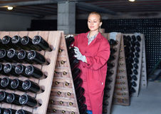 制服的妇女与瓶存贮一起使用在酿酒厂cel折磨 库存照片