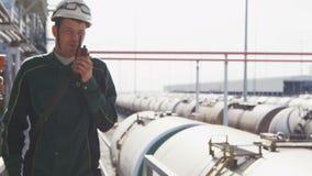 制服的工程师走向照相机反对煤气管 股票录像