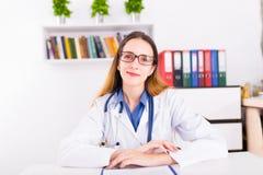 制服的年轻女性医生在医生` s ofice写文件的 免版税库存照片