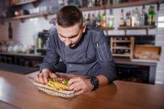 制服的快乐的厨师,计划一个可口汉堡包用在篮子的油煎的土豆 免版税库存图片