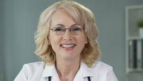 制服的成熟白肤金发的女性医生微笑入照相机,医疗保健诊所的 影视素材