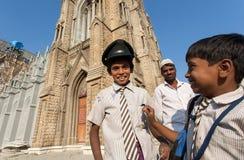 制服的男小学生获得乐趣在天主教学校的庭院 图库摄影