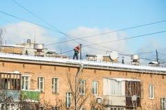 制服的管理员在暴风雪以后清洗雪从屋顶 库存图片