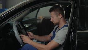 制服的英俊的技工在自动服务工作 汽车修理和维护 进行引擎诊断与 股票录像