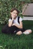 制服的逗人喜爱的基本的女小学生与背包坐草 库存图片