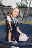 制服的逗人喜爱的基本的女小学生在操场 免版税库存图片
