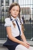 制服的逗人喜爱的基本的女小学生在操场 图库摄影