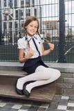 制服的逗人喜爱的女小学生在操场 免版税库存图片