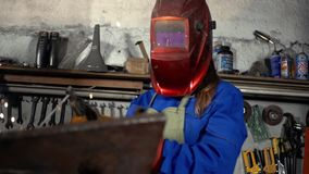 制服的逗人喜爱的焊工女孩在车库与焊接器材一起使用 妇女在艺术的` s工作 影视素材