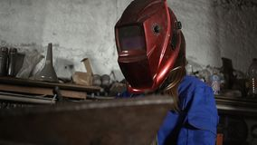 制服的逗人喜爱的焊工女孩在车库与焊接器材一起使用 妇女在艺术的` s工作 股票录像