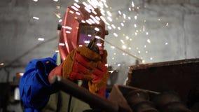 制服的逗人喜爱的焊工女孩在车库与焊接器材一起使用 妇女在艺术的` s工作 股票视频