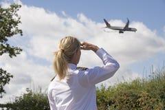 制服的飞行员观看在天空的一架喷气式客机 免版税库存照片