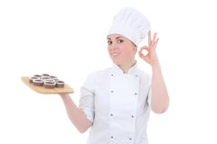 制服的年轻可爱的厨师妇女用嘘巧克力松饼 库存图片