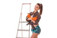 制服的年轻可爱的深色的妇女做与看照相机和微笑的梯子的整修被隔绝  库存图片