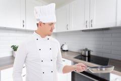 制服的年轻英俊的人厨师有在现代成套工具的煎锅的 免版税图库摄影