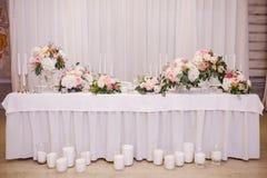 制表与白花和蜡烛的装饰婚礼聚会的 免版税库存照片