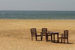 制表和在一个空的海滩的四把椅子 免版税库存照片