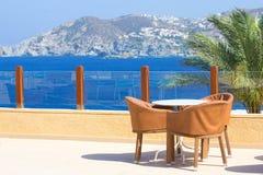 制表和在大阳台的三把椅子有海视图 免版税图库摄影