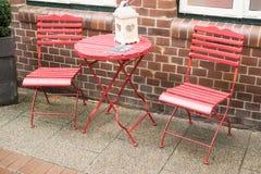 制表和在红色的两把椅子与水下落 库存照片