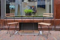 制表和在边路的两把椅子在商店前面 库存图片