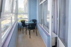 制表和在阳台的三把椅子一个多层的公寓的公寓的 免版税图库摄影