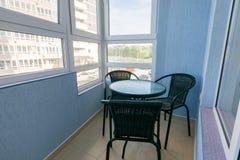 制表和在阳台的三把椅子一个多层的公寓的公寓的 免版税库存图片
