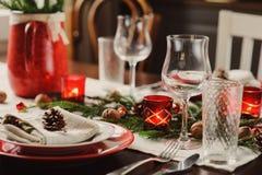 制表设置庆祝圣诞节和新年假日 在经典红色的欢乐桌和绿色在家与土气细节 库存照片