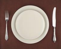 制表设置 米黄板材、葡萄酒叉子和刀子在一张棕色亚麻制桌布 免版税库存照片