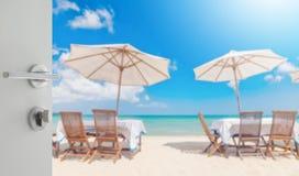 制表集合和伞的被打开的白色门在海滩 库存照片