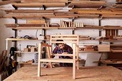 制造一个木椅子框架的工匠在他的演播室 库存图片
