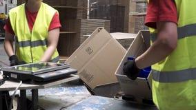制造业工作者的手的特写镜头视图投入被包装的产品的在纸板箱,在出口前或 免版税库存照片