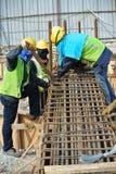 制造地梁增强酒吧的建筑工人 免版税库存照片