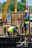 制造地梁钢增强酒吧的两名建筑工人 免版税图库摄影
