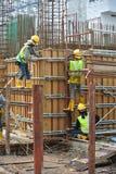 制造增强混凝土墙形式的建筑工人工作 库存图片