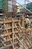 制造木材专栏模板的建筑工人在建造场所 图库摄影