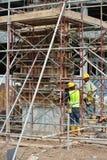 制造木材专栏模板的建筑工人在建造场所 免版税库存照片